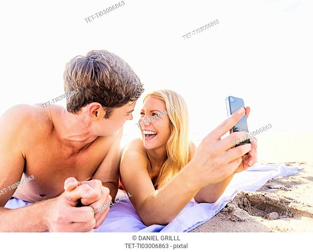 Portrait of young couple lying on blanket on beach, using smart phone
