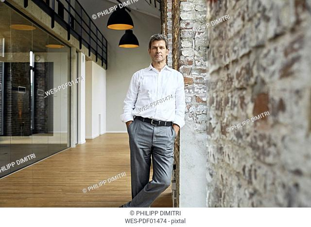 Portrait of confident businessman leaning against brick wall in modern office