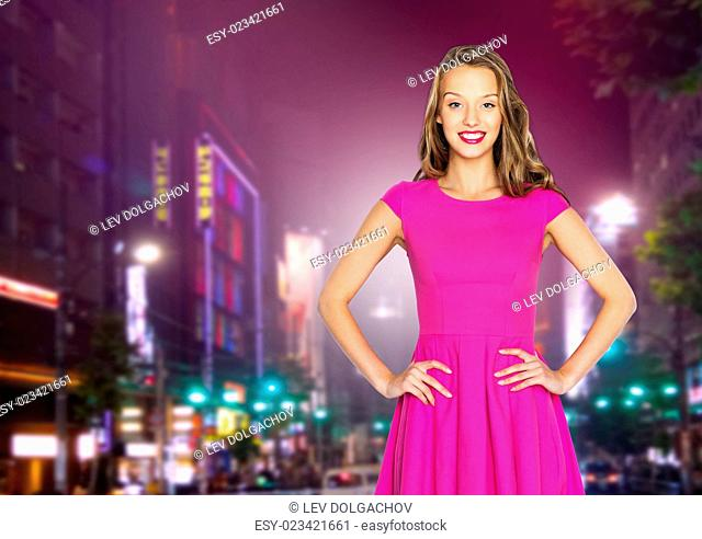 beauty, people, holidays, nightlife and fashion concept - happy young woman or teen girl in pink dress over night city street background