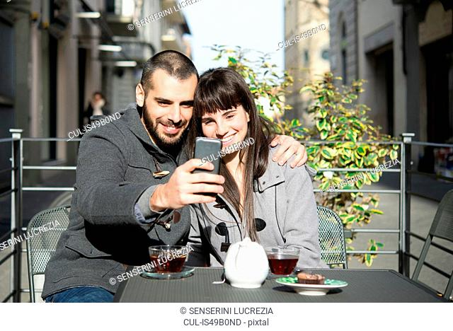 Young couple sitting outside cafe, taking selfie, using smartphone