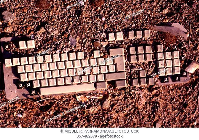 Computer keyboard half buried in earth. Next to Glorias, Barcelona. Catalonia. Spain