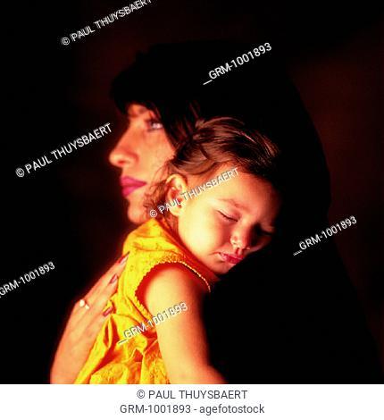 Arab mother holding her sleeping baby girl