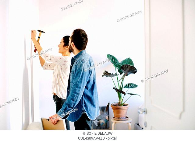 Young couple hammering in nail for framed picture in living room