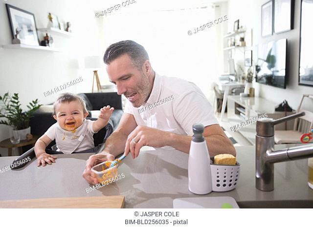 Father feeding happy baby son