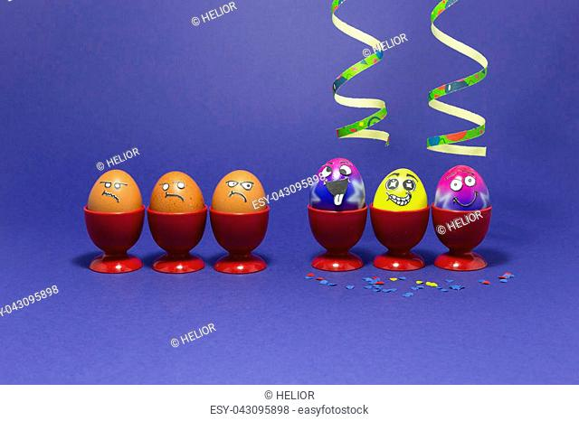 Group of colorful painted Easter eggs with funny cartoon style faces, confetti and paper streamers and group of grumpy looking brown eggs in red plastic egg...