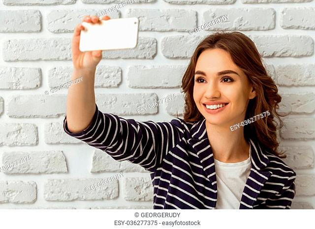 Beautiful young woman making self-portrait on a smartphone on a brick wall background