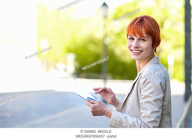 Smiling young woman outdoors with digital tablet