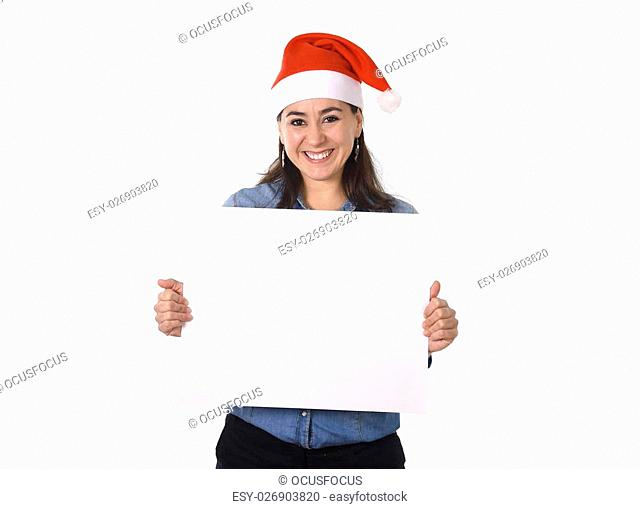 young attractive Hispanic woman wearing Santa Claus Christmas hat and blue shirt holding blank billboard or placard sign as copy space for adding text...