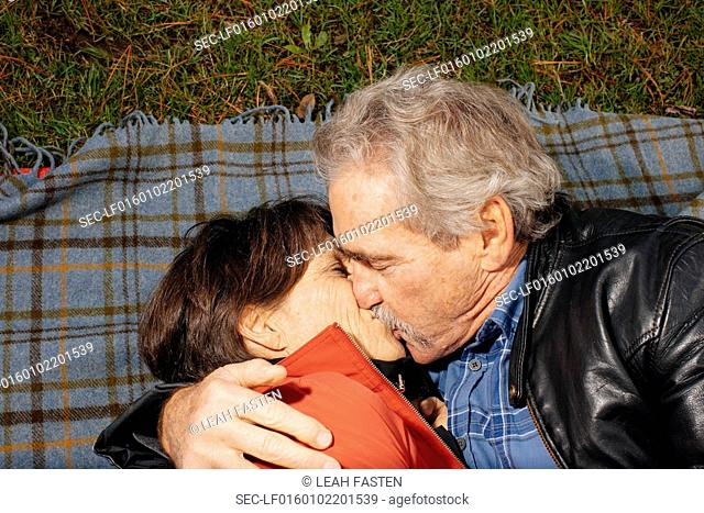 Senior couple lying down on blanket and kissing in park