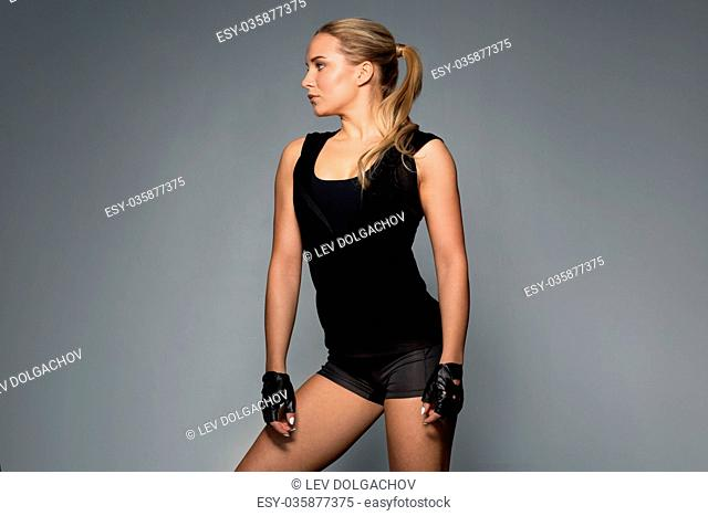 sport, fitness and people concept - young woman in black sportswear posing in gym