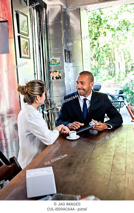 Business man and woman in cafe with digital tablet