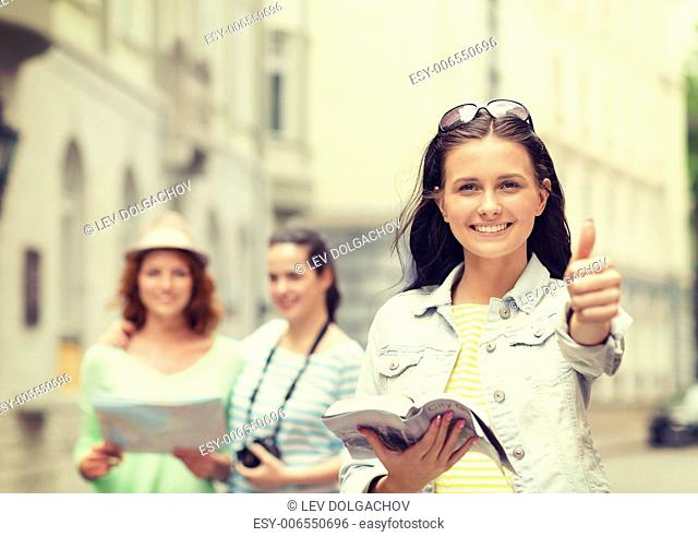 tourism, travel, holidays and friendship concept - smiling teenage girls with city guide, map and camera showing thumbs up outdoors