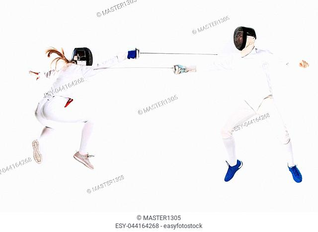 The woman and man wearing fencing suit practicing with sword against gray studio background