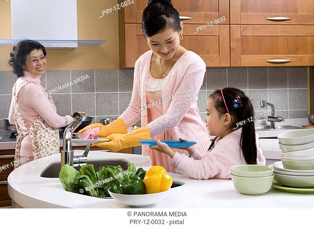 Mother with daughter washing plates while grandmother cooking food in background