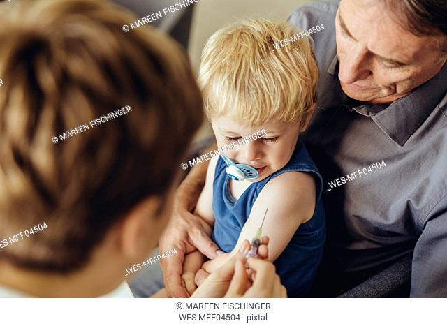 Father holding son while being vaccinated by pedeatrician
