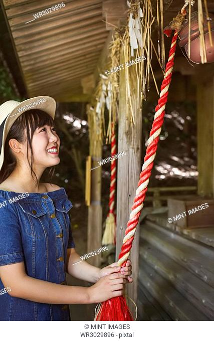 Young woman wearing blue dress and hat pulling on red rope at Shinto Sakurai Shrine, Fukuoka, Japan
