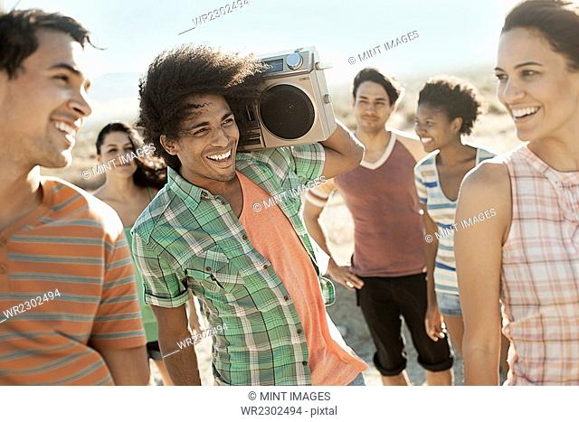 Group of young people, men and women walking on the open road with a boombox
