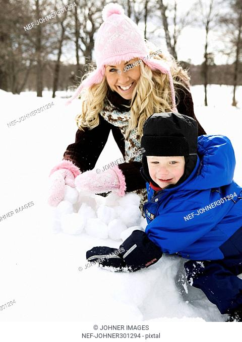 A woman and a boy building a snowball lantern