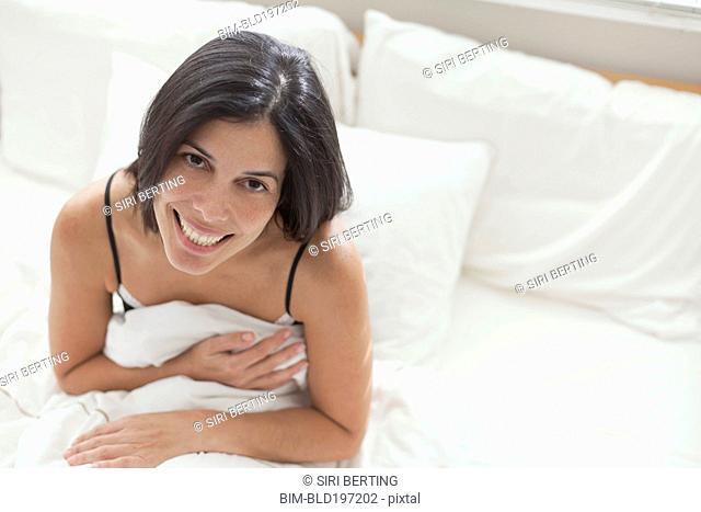 Smiling Hispanic sitting in bed