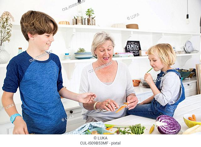 Senior woman and grandchildren preparing vegetables at kitchen table