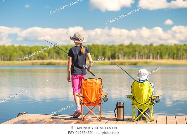 a girl and a boy spend time on the pier, children with fishing rods are fishing