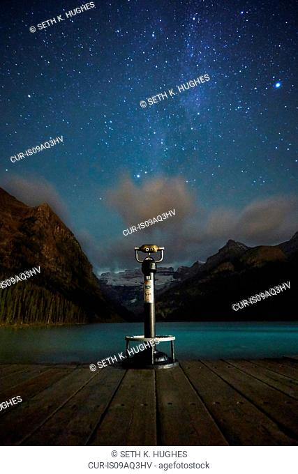 Viewing binoculars against starry sky, beside Lake Louise, Alberta, Canada