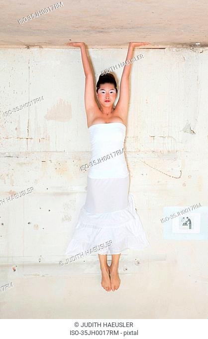 Woman in gown doing headstand
