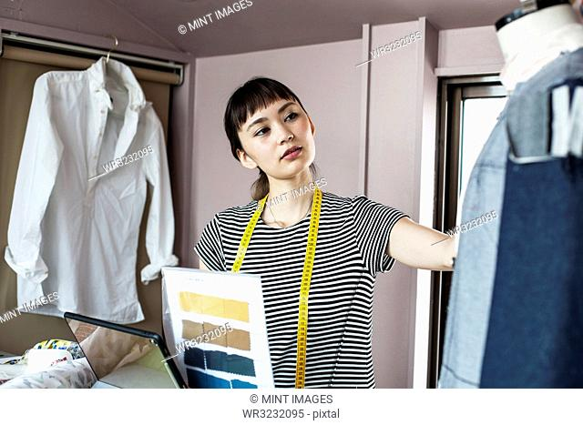 Japanese female fashion designer working in her studio, looking at garment on dressmaker's model