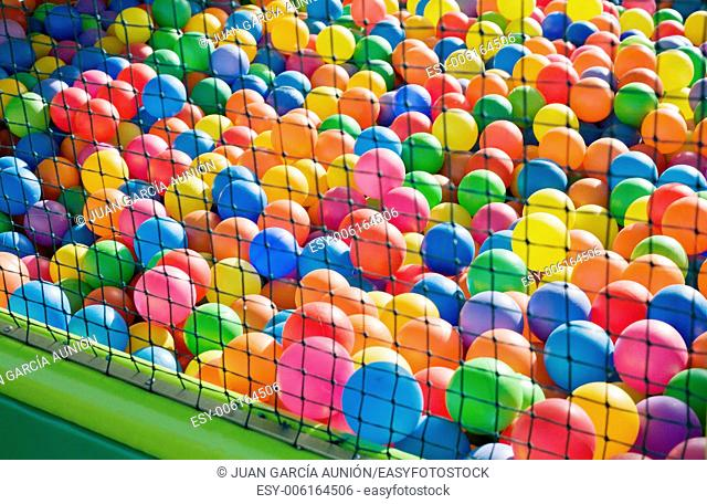 Photo of a playground for children, full of colorful plastic balls behind the net
