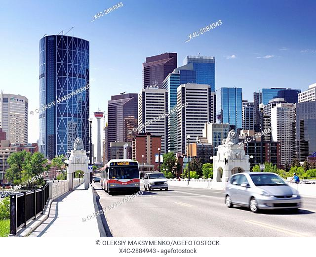 Calgary Transit bus and cars on Centre Street Bridge with Calgary city downtown skyline and Calgary tower in the background