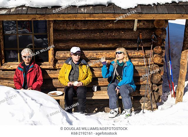 Three women skiers sit by a log cabin in winter at the Elizabeth Parker hut, Lake O'Hara, Yoho National Park, British Columbia, Canada