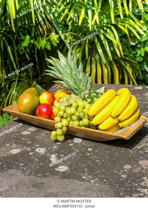 Wooden plate of bananas, pineapple, green grapes, mango and nectarines