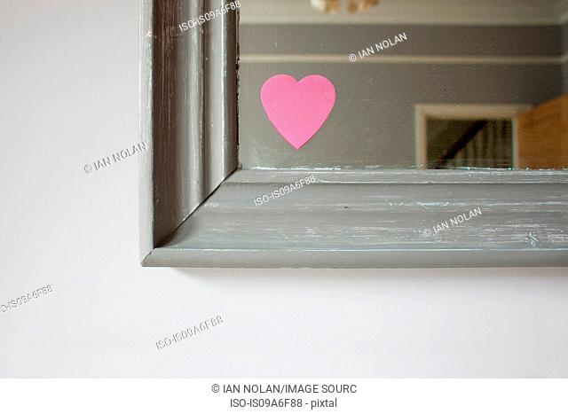 Heart shaped adhesive note on mirror