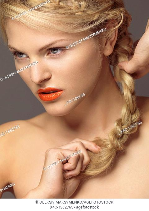 Beauty portrait of a young woman with bright orange lipstick