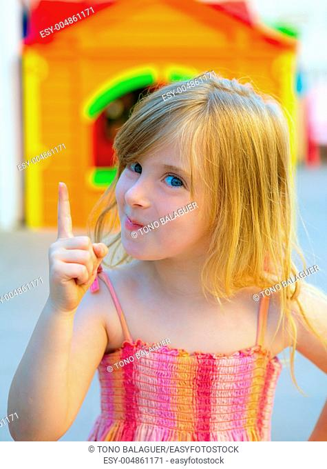 Blond kid girl funny gesture finger up in playground with sundress