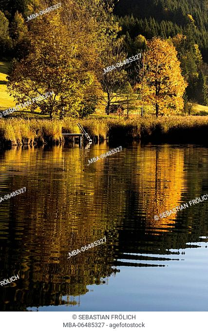 Autumnal trees and bridge on the shore of the Geroldsee between Garmisch-Partenkirchen and Mittenwald
