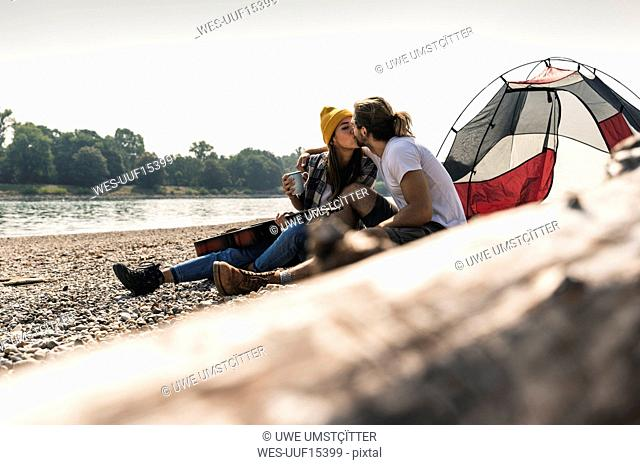 Young couple with guitar kissing at a tent at the riverside