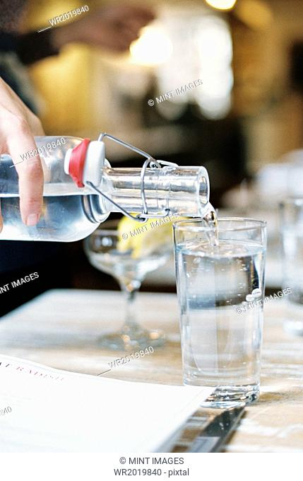 A hand pouring water from a bottle with a clip top into a glass