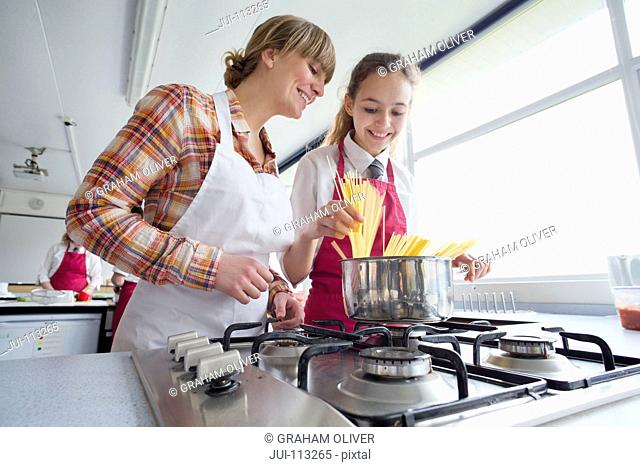 Teacher teaching high school student cooking pasta in home economics class