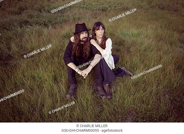 Bohemian Couple Sitting in Tall Grass