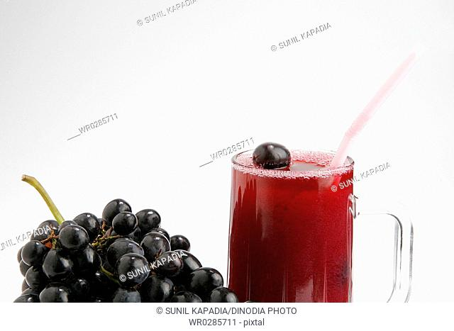 Fruit , black grapes with glass of juice against white background