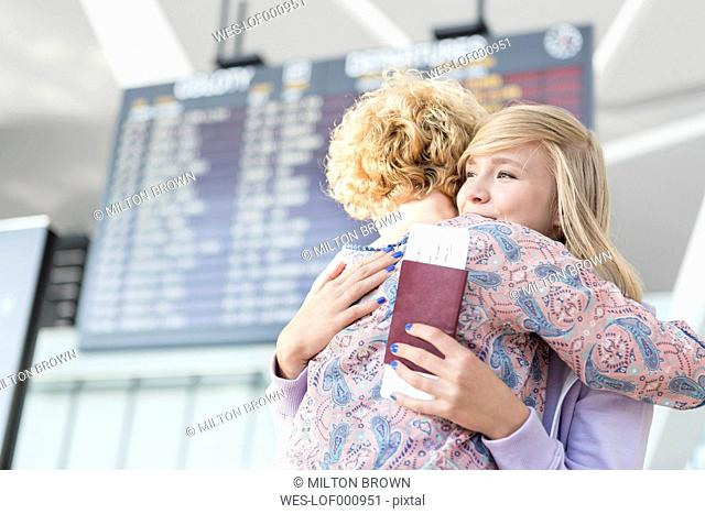 Mother hugging daughter at the airport