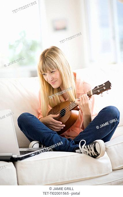 Woman playing ukulele while using laptop