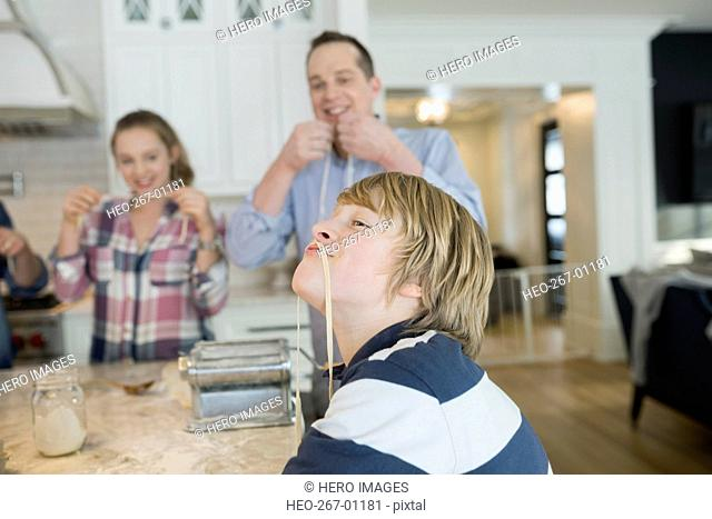 Playful boy with long noodle mustache in kitchen