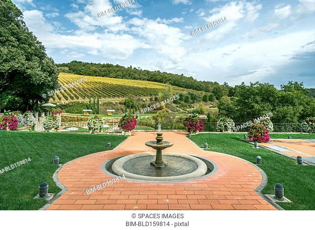 Fountain and walkway in landscaped grounds over rural fields, Radda in Chianti, Siena, Italy