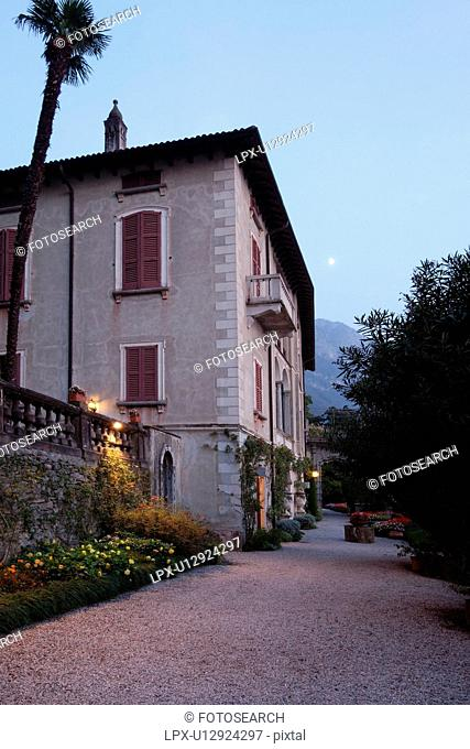 Ornamental gardens and pathway in Villa Monastero with terracotta pots on columns, flower beds, and villa annex, autumn evening at dusk with moonrise and blue...