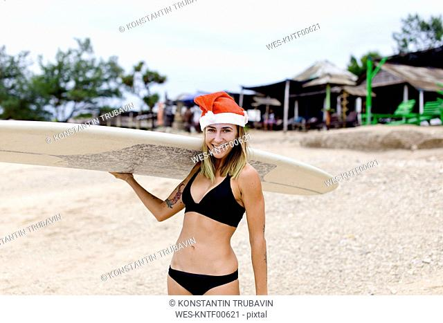 Indonesia, Bali, smiling woman carrying surfboard on the beach wearing Santa hat