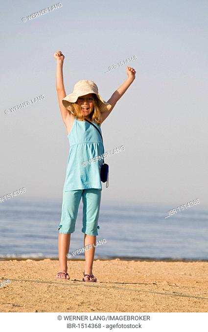 Glad girl, eight years, cheering at the beach