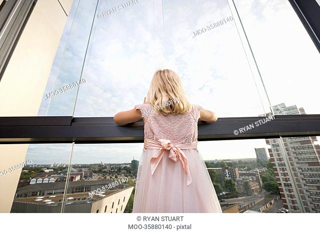 Rear view of girl looking through window