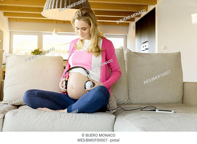Pregnant woman sitting on couch holding headphones to her belly